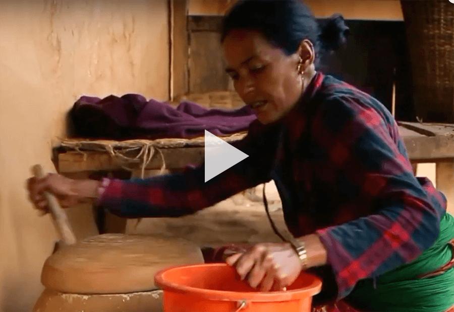 A woman crushing corn in a cultural way