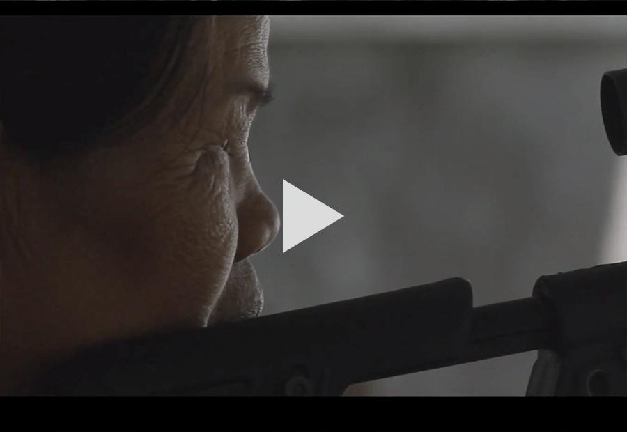Asian Woman looking through a rifle