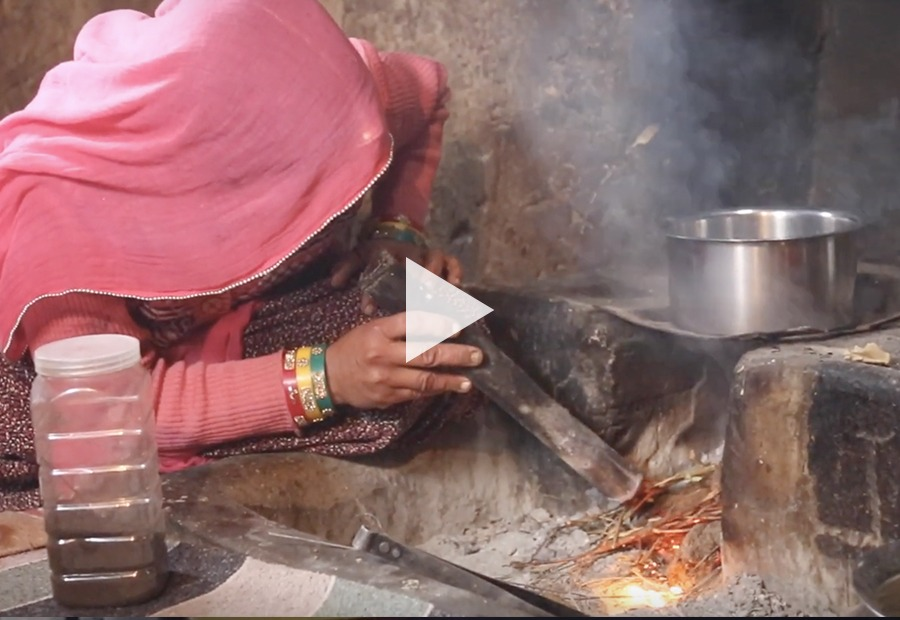 woman turning on kitchen fire