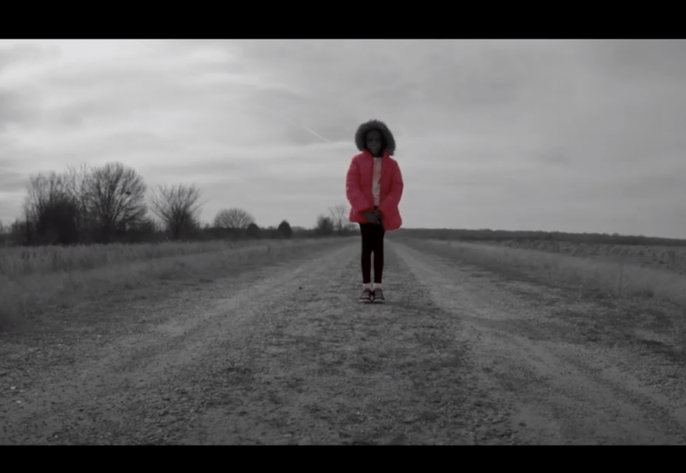 A African-American girl standing in the middle of a dirt road